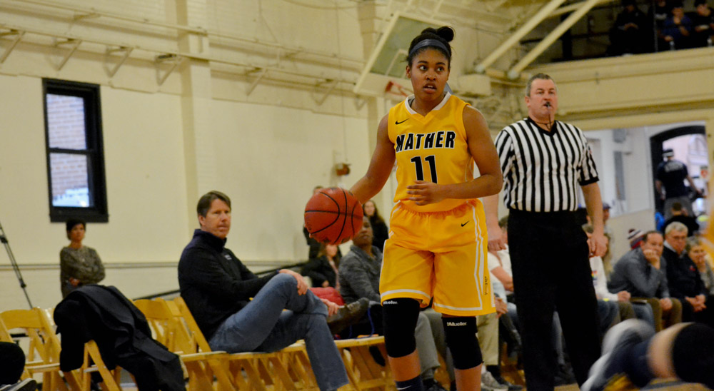 Photo of a women's basketball player wearing a Mather College jersey dribbling the ball during a throwback game