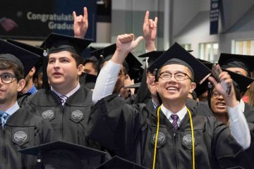 Several graduates cheering during 2018 commencement ceremony