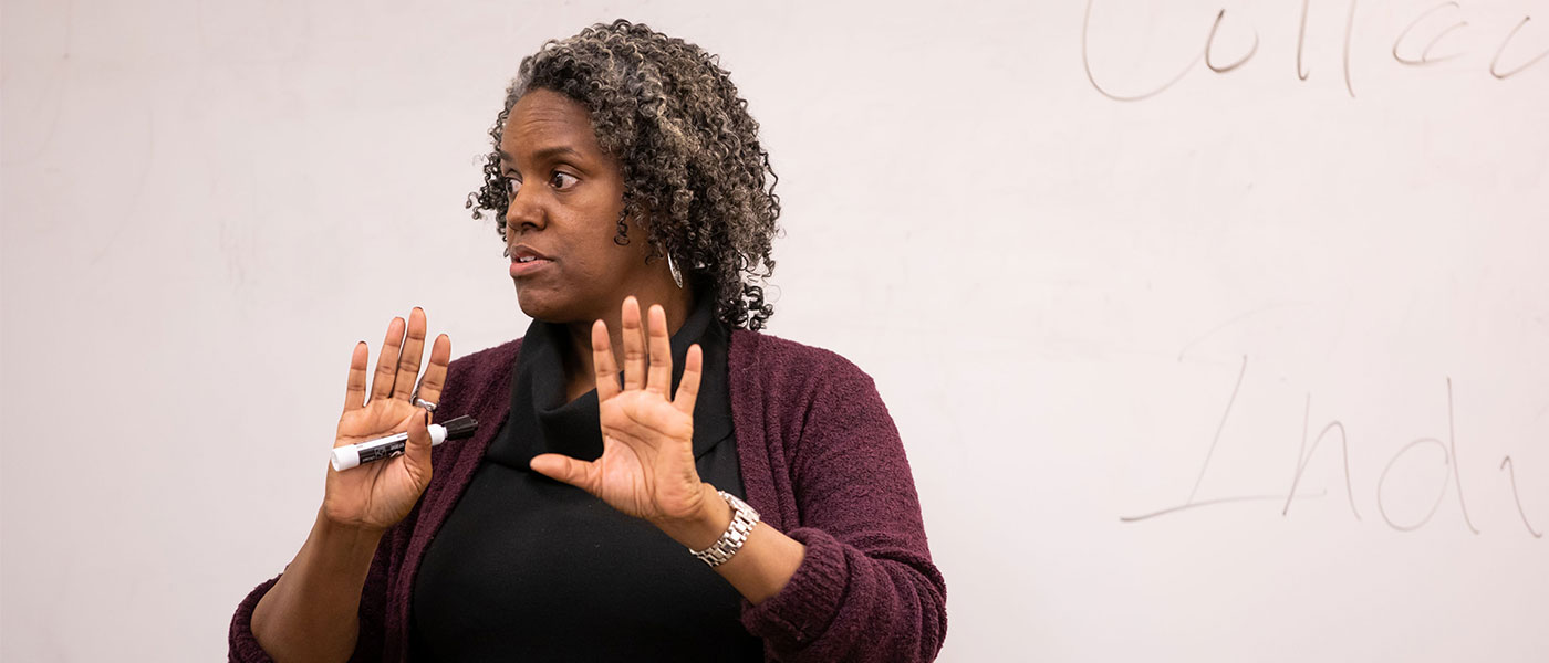 Photo of Joy Bostic teaching with a dry erase board behind her