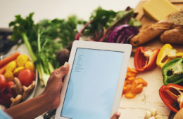 patient consulting electronic tablet while at a table filled with vegetables