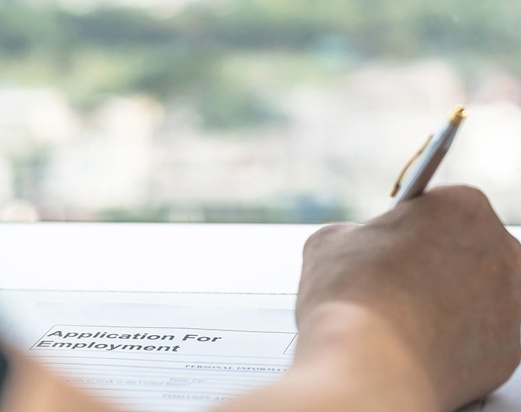 Hand writing with a pen onto a job application