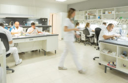 People working in a dental lab setting, with people at work stations around the room