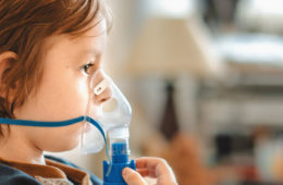 a child receiving oxygen at home, while sitting on the couch