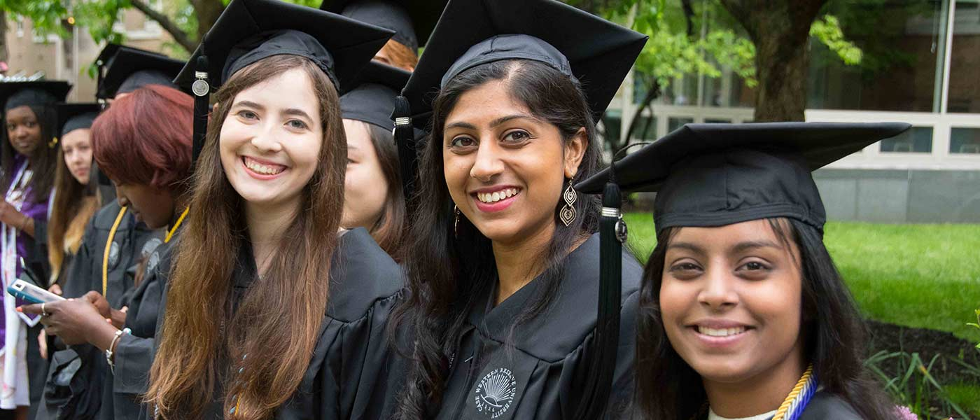 Three female CWRU graduates pose for a photo outside during commencement 2018