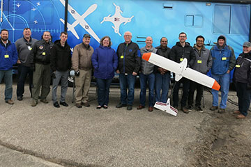A group photo of the participants in the flight test and the small airplane