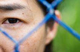 close up photo showing a girl looking through fence