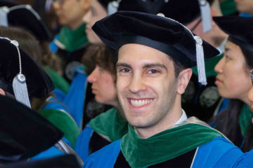 Photo of a doctoral student in regalia smiling at the camera during commencement while surrounded by other graduates