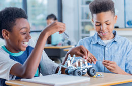 two young boys working on small metal car
