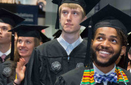Students standing and smiling during commencement ceremonies