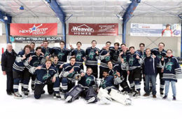 Photo of the ice hockey team posing for a photo on the ice