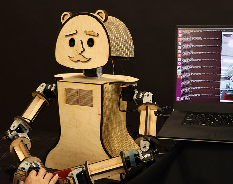 a woman and a small robot, which is learning to read her emotions