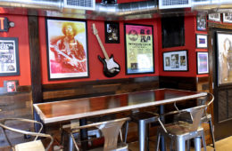 The interior of the Dave's Cosmic Subs on campus with a table and chairs and decor, including posters and guitar decor on the walls