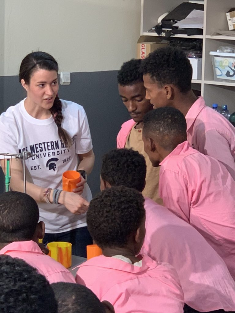 Blaire Volbers surrounded by students in Ethiopia during a science demonstration