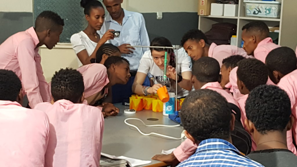 Blaire Volbers leads a science demonstration while surrounded by students in Ethiopia