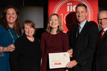 Photo of five individuals posing for photo while holding award during IIE Summit