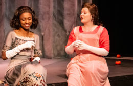 "Two female students on stage during a scene of ""As You Like it"""