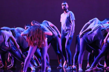 Photo from a MaDaCol performance with one dancer standing in a circle of others