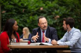Professor Jonathan Adler, with textbooks open, talking with students at the law school on an outdoor picnic table.