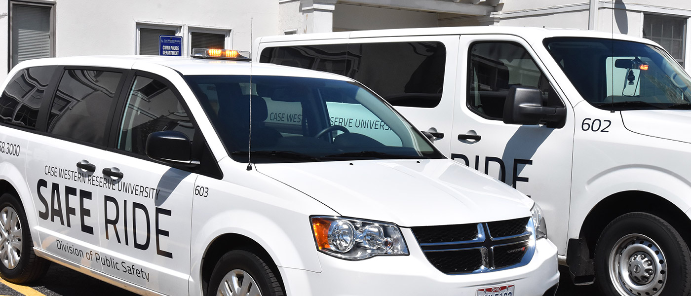 Photo of two Safe Ride vans, one with yellow light on top and the other with light on windshield