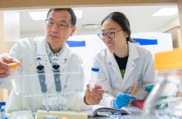 Photo of Lin Mei holding two vials as he and a student examine them in the lab