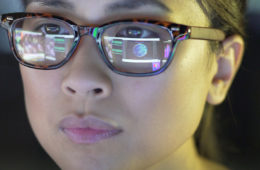 Close up photo of a woman's face as she stares at a computer screen, reflecting onto her glasses