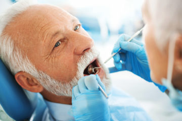 Photo of an elderly man with dental instruments in his mouth as dentist works on his teeth
