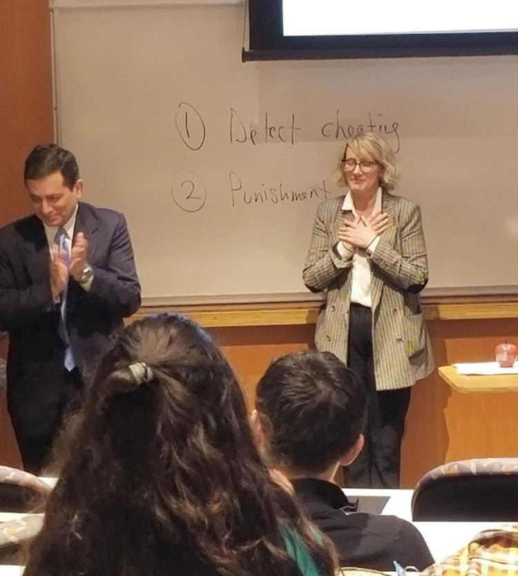 Photo taken from behind students in class showing Jenny Hawkins' reaction when surprised with the Wittke and Jackson Awards
