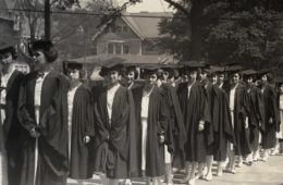 Black and white photo of Mather College women graduates wearing graduation robes in two lines during their procession during commencement
