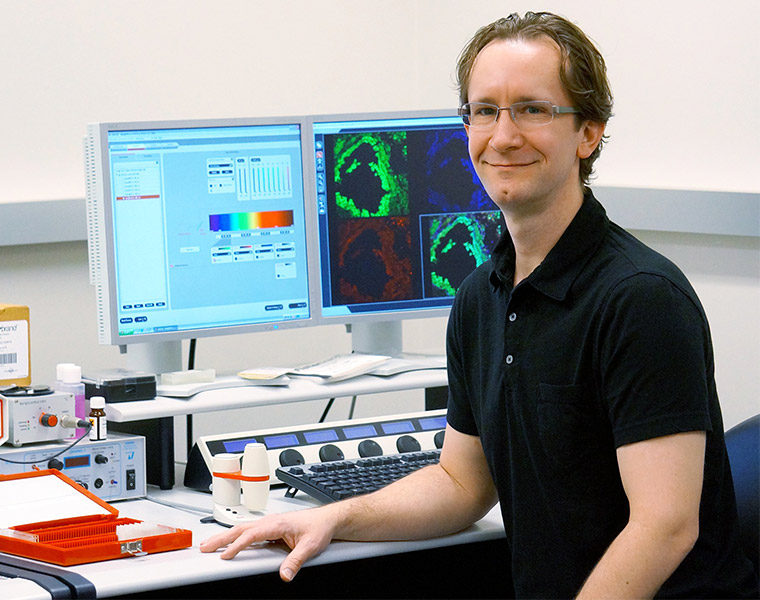Photo of Brian Cobb sitting at a desk looking at the camera with computer screens behind him displaying research