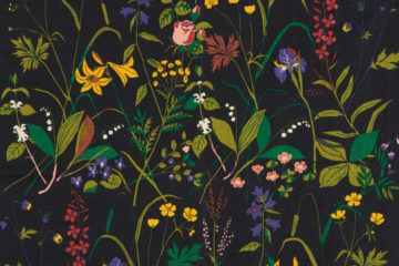 Photo of a Swedish textile that has green leaves and colorful flowers against a black background
