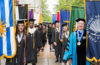 Photo of banner guards lined up at commencement holding the heraldic banners for all of the schools