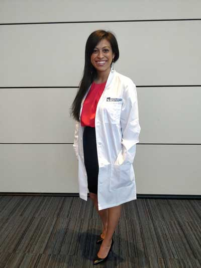 Case Western Reserve University dental student Lizzeth Moreno standing, wearing a white coat