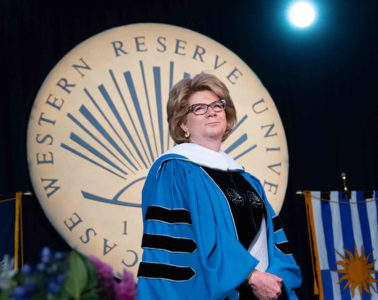 Photo of Beth Mooney standing in front of the Case Western Reserve University seal during commencement