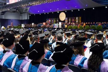 Photo of the stage during CWRU commencement with doctoral graduates sitting in the foreground