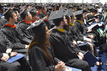 Photos of master's graduates look toward the stage during 2019 university-wide commencement ceremony