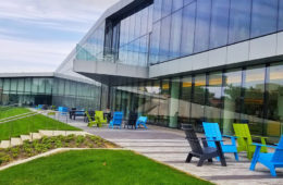 Exterior of the Tinkham Veale University Center showing tables and chairs set up on the patio area