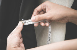 Close up photo on the hands of a fashion designer as she measures a jacket