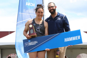 Photo of Cassandra Laios holding a trophy and posing for a photo with Rocco Mitolo while both hold a sign that says hammer