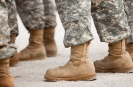 Close up photo on the legs and feet of military members as they stand in formation