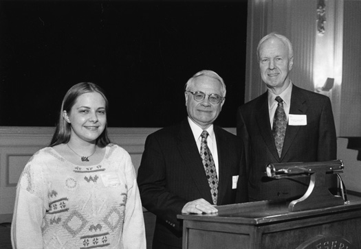 Richard Zdanis stands at a podium and poses for a photo with a woman and David Auston