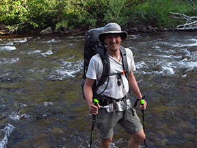 Researcher Nicholas Sutfin standing in shallow St. Vrain Creek, a 32-mile-long tributary of the South Platte River in north central Colorado.