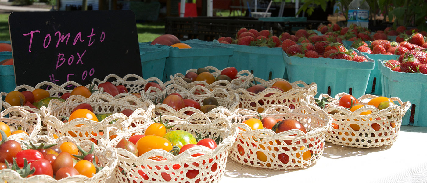 Photo of a display at a farmers market with a sign advertising tomatoes, tomatoes in decorative baskets and strawberries in baskets