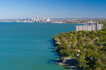 Aerial photo of the Lake Erie coastline with Lakewood in the foreground and the Cleveland skyline in the background