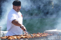Photo of a chef grilling outside with smoke behind him