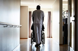a male nurse pushes a man down the hallway at a nursing home.