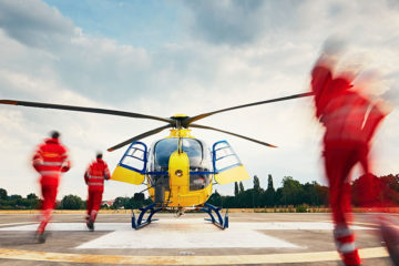 a medical helicopter preparing to take off, as crew members run to it