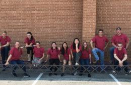 Photo of 13 members of the Steel Bridge Team with their bridge design