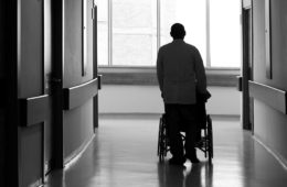 Photo of a man pushing a wheelchair down a nursing home hallway