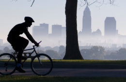 Silhouette of a person on a bicycle with the Cleveland skyline in the background