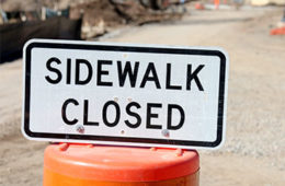 "Photo of a sign that says ""sidewalk closed"" on top of a construction barrel with dirt in the background"